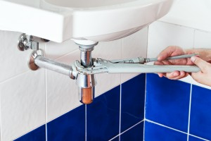 plumber repairing metallic drain of white sink by pipe-wrench